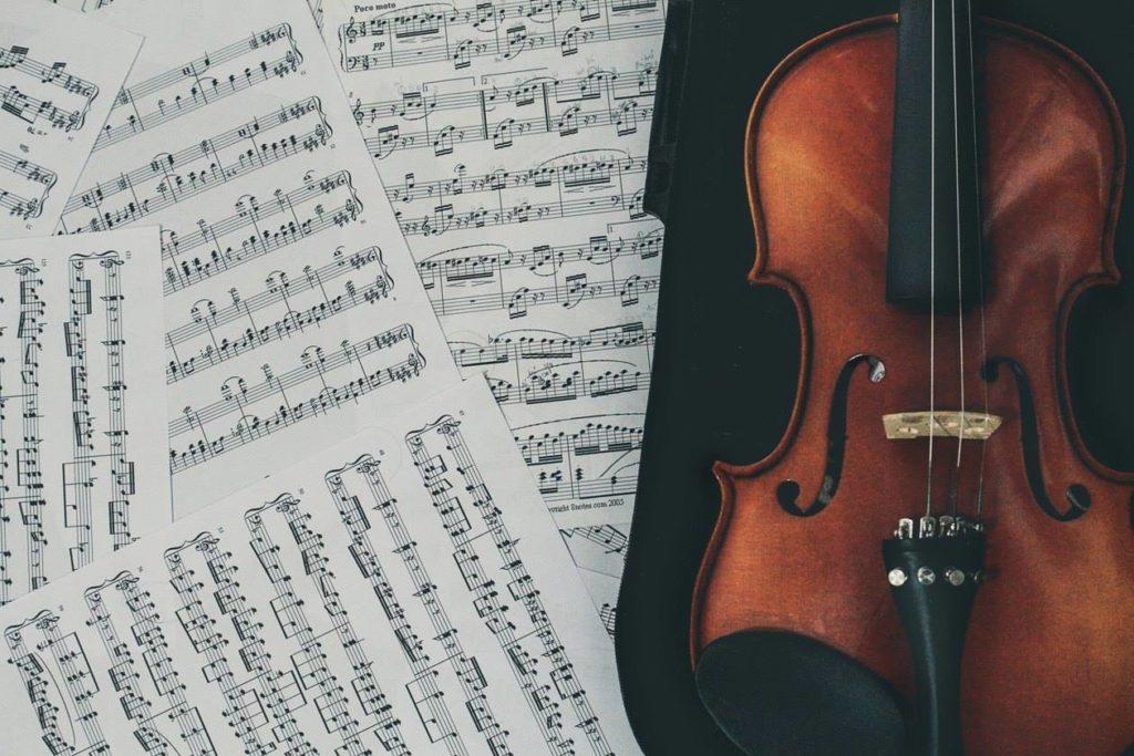 un violino sopra degli spartiti di musica a rappresentaree i post musicali
